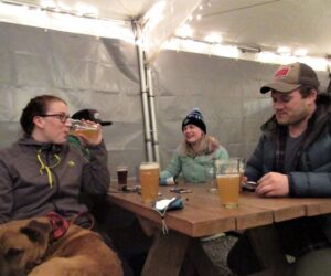 Four people sit at an outdoor patio at Fishers Brewing Company