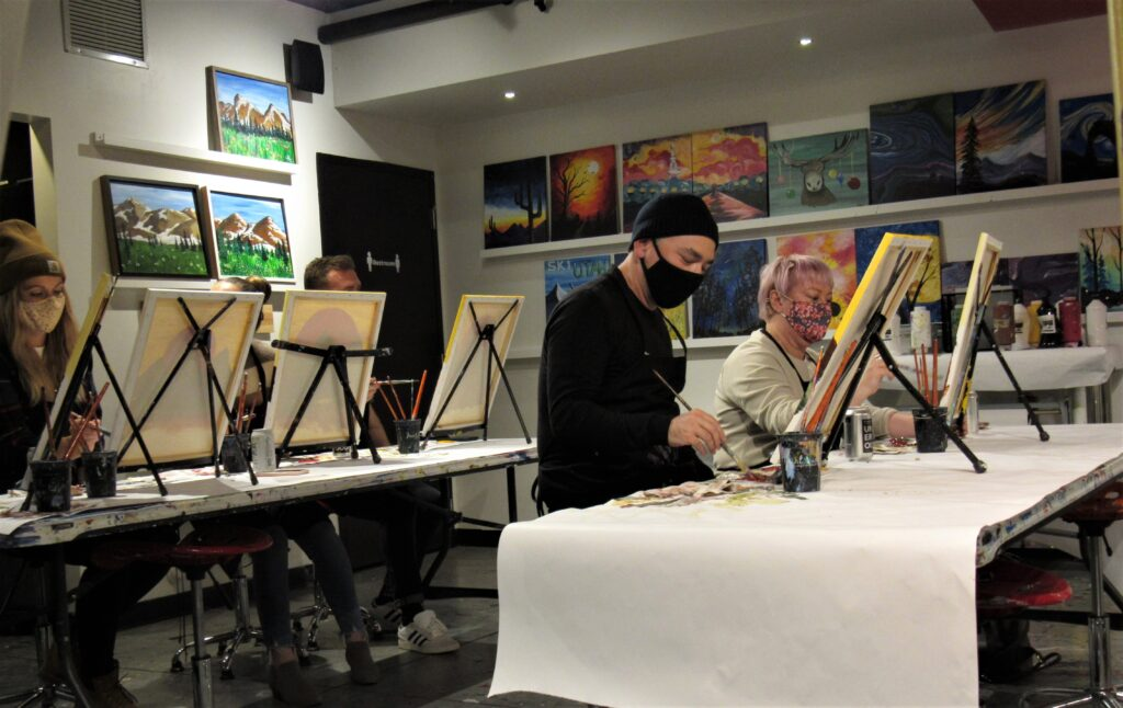 The Paint Mixer, a local art studio, leads participants through a wine and paint night called Fire Sun.