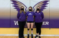 Audrey Green stands with her coaches after a volleyball game.