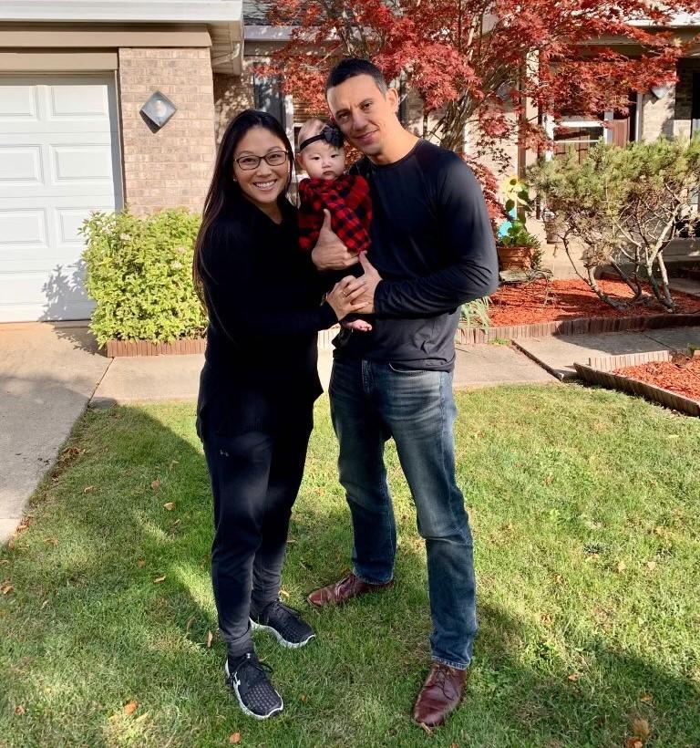 Malia Shoji stands with her newborn and husband.