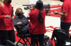 Malia Shoji works while holding her baby at the Huntsman Center.